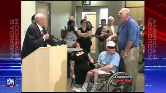 U.S. Rep. John Dingell, D-Mich, (b. 1926) is confronted at lectern by a younger Old Guy